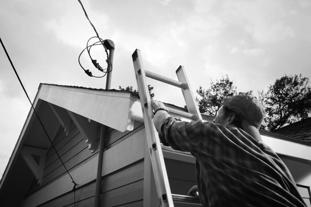 Image of man climbing ladder to roof where power lines attach to home