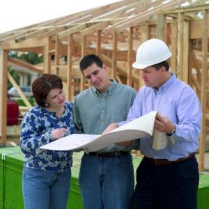 Image of couple with building plans with contractor in front of new construction
