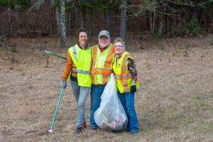 Three volunteers cleaning up roadside ditches near Lake Bemidji State Park