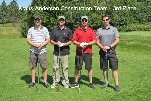 3rd place team, Kraus Anderson, on golf course holding golf clubs