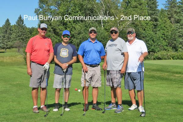 2nd place team, Paul Bunyan Communications on golf course with golf clubs